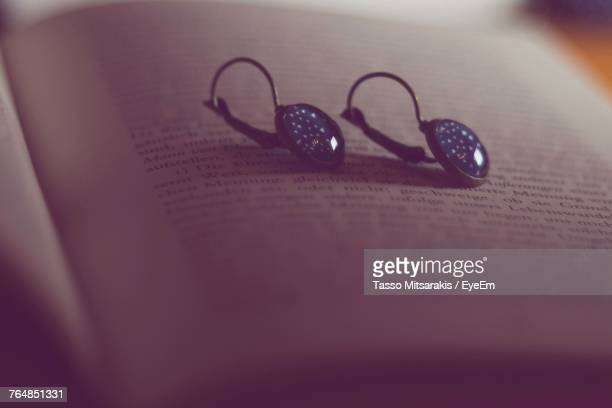 Close-Up Of Earrings On Book
