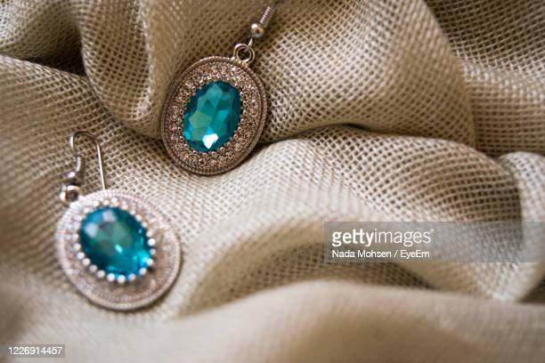 close-up of earrings on cloth - earring stock pictures, royalty-free photos & images
