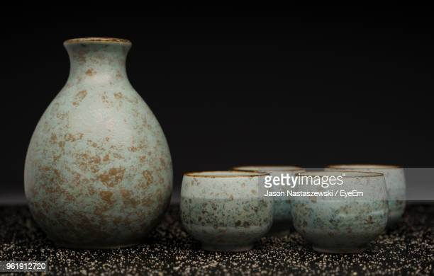 close-up of earthenware on table against black background - craft product stock photos and pictures