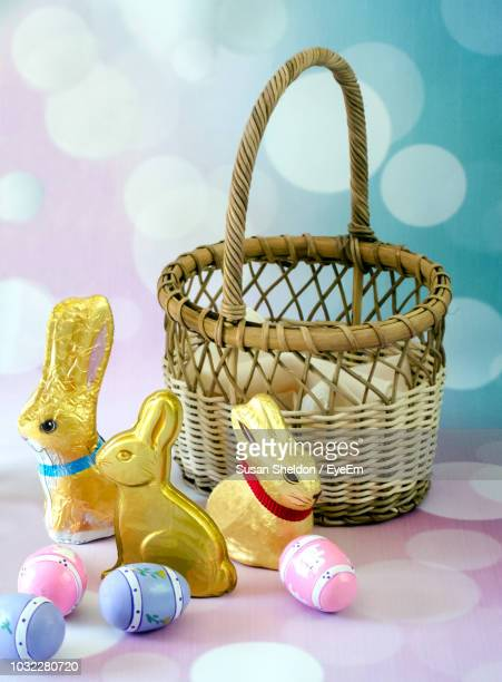 close-up of easter bunnies with eggs and wicker basket against abstract backgrounds - easter candy stock pictures, royalty-free photos & images