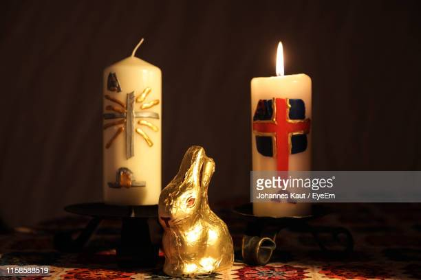 close-up of easter bunny and illuminated candles on table during christmas - ravensburg stock-fotos und bilder