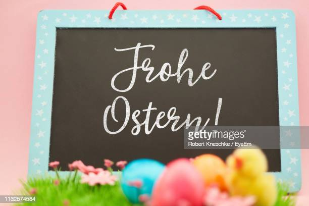 close-up of easter eggs and writing slate with text - happy easter text stock pictures, royalty-free photos & images