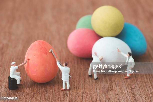 close-up of easter eggs with figurines on wooden table - human representation stock pictures, royalty-free photos & images