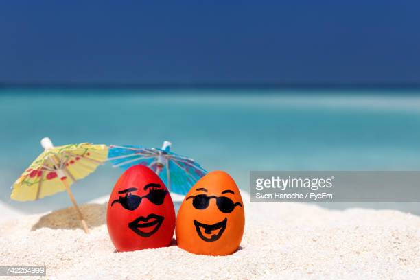 close-up of easter eggs with small beach umbrellas on sand at beach - easter beach stock pictures, royalty-free photos & images