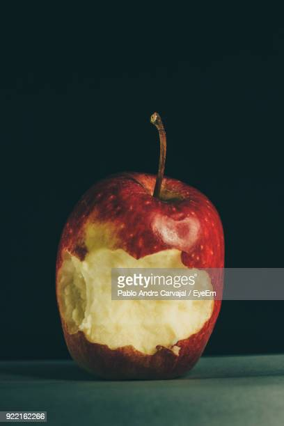 close-up of eaten apple on table against black background - carvajal stock photos and pictures
