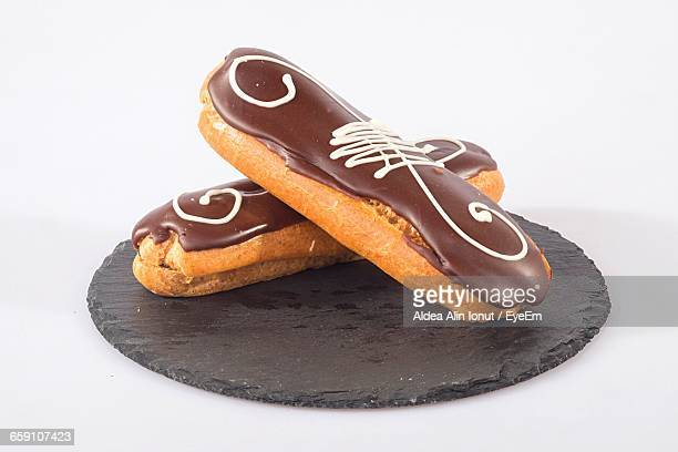 Close-Up Of Eclairs Against White Background