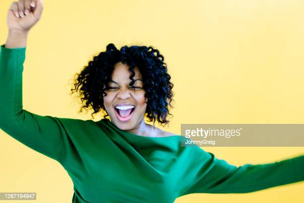 close-up of ecstatic young black woman laughing and dancing - motion stock pictures, royalty-free photos & images