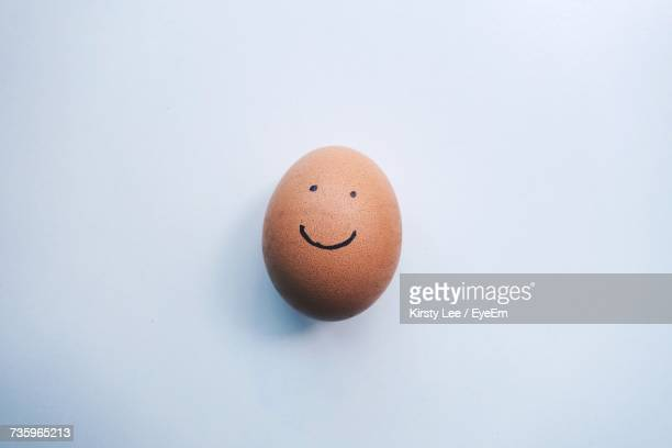 Close-Up Of Egg With Face Against White Background