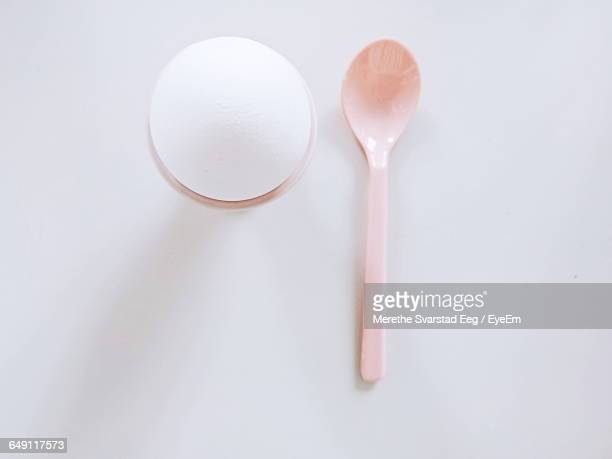 Close-Up Of Eggcup And Spoon Over White Background