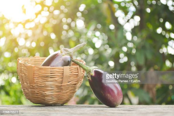 Close-Up Of Eggplants And Wicker Basket On Wooden Bench