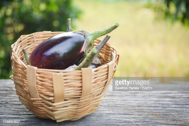 Close-Up Of Eggplants In Wicker Basket On Wooden Bench