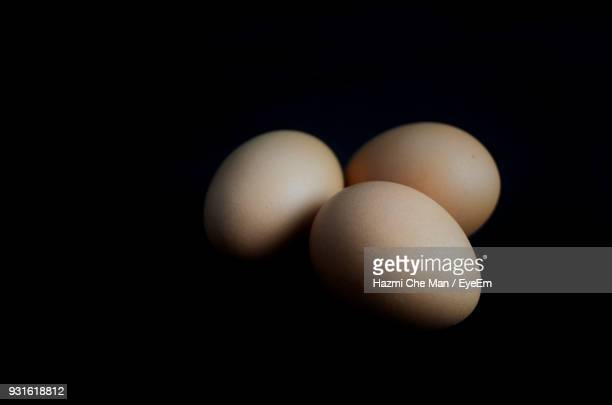 close-up of eggs against black background - frische stockfoto's en -beelden
