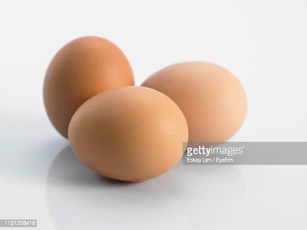 close-up of eggs against white background - small group of objects stock pictures, royalty-free photos & images