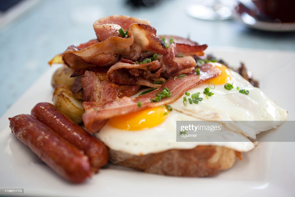 A closeup of eggs, bacon, ham, and sausage on top of toast : Stock Photo