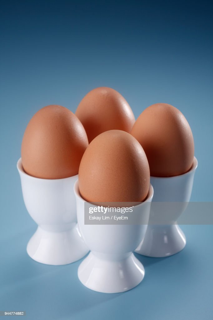 Close-Up Of Eggs In Cups On Colored Background : Stock Photo