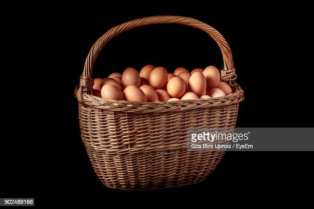 Close-Up Of Eggs In Wicker Basket Against Black Background