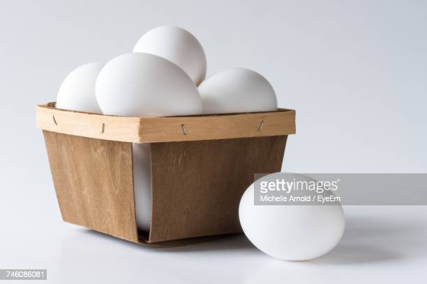 close-up of eggs in wooden container over white background - oval shaped objects stock pictures, royalty-free photos & images