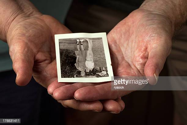 closeup of elderly couple hands holding old honeymoon photo - time travel stock pictures, royalty-free photos & images