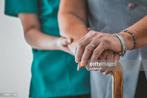 close-up of elderly woman holding walking stick in the nursing house - osteoporosis stock pictures, royalty-free photos & images