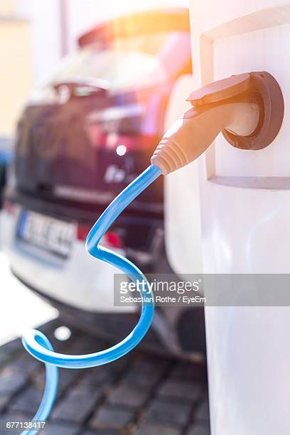 close-up of electric car battery charger at station - hybrid car stock photos and pictures