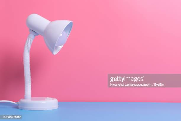 close-up of electric lamp on table against wall - two tone color stock pictures, royalty-free photos & images