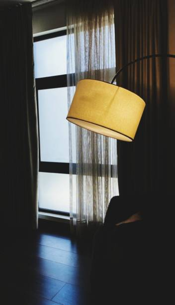 Close-Up Of Electric Lamp On Table By Window At Home