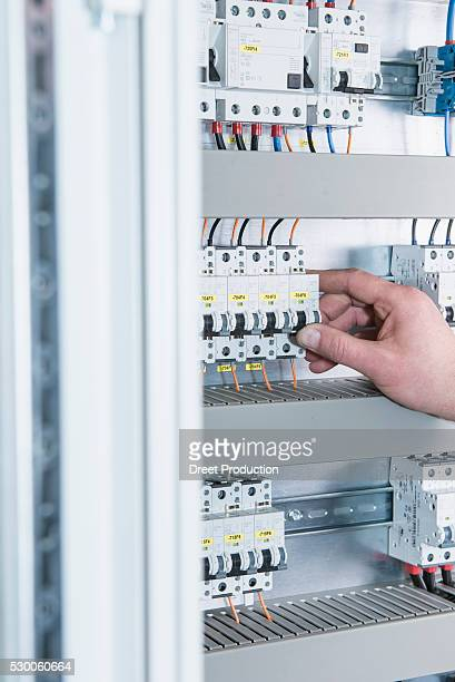 Close-up of electrician switching electrical fuse in distribution fusebox, Munich, Bavaria, Germany