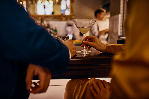 Close-up of elegant couple having a drink at the counter in a bar - gettyimageskorea