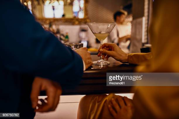 close-up of elegant couple having a drink at the counter in a bar - dating stock pictures, royalty-free photos & images