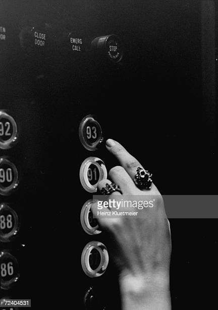 Close-up of elevator button panel, in residential section of the John Hancock Bldg., with a woman's hand at button.