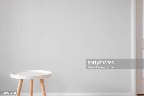 close-up of empty chair on table against wall - muted backgrounds stock pictures, royalty-free photos & images