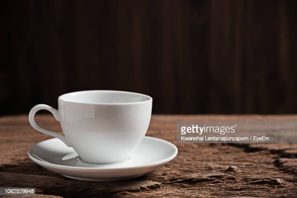 close-up of empty coffee cup on wooden table - saucer stock pictures, royalty-free photos & images