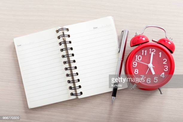 Closeup of empty opened notebook with pen and alarm clock on table.