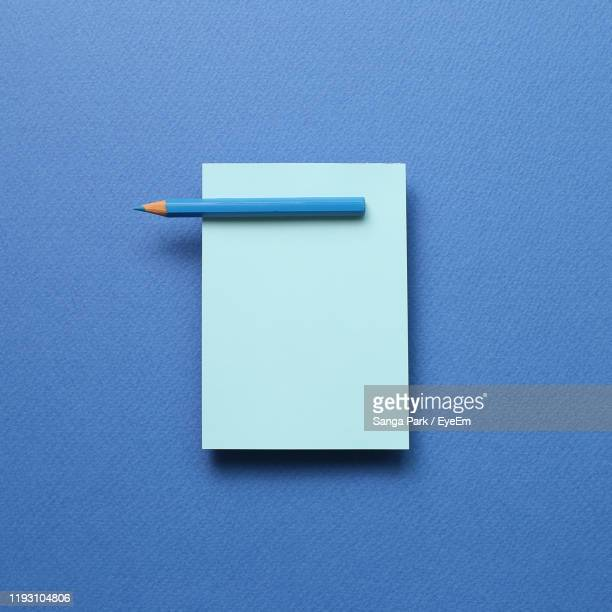 close-up of empty paper against blue background - note pad stock pictures, royalty-free photos & images