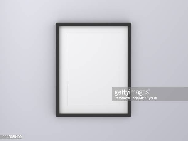 close-up of empty picture frame on white wall - dipinto foto e immagini stock