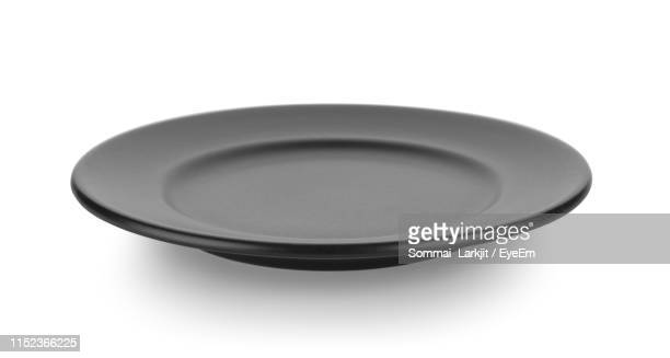 close-up of empty plate against white background - 皿 ストックフォトと画像