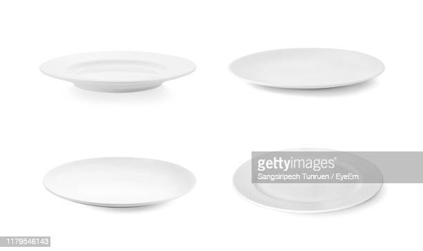 close-up of empty plates against white background - plate stock pictures, royalty-free photos & images