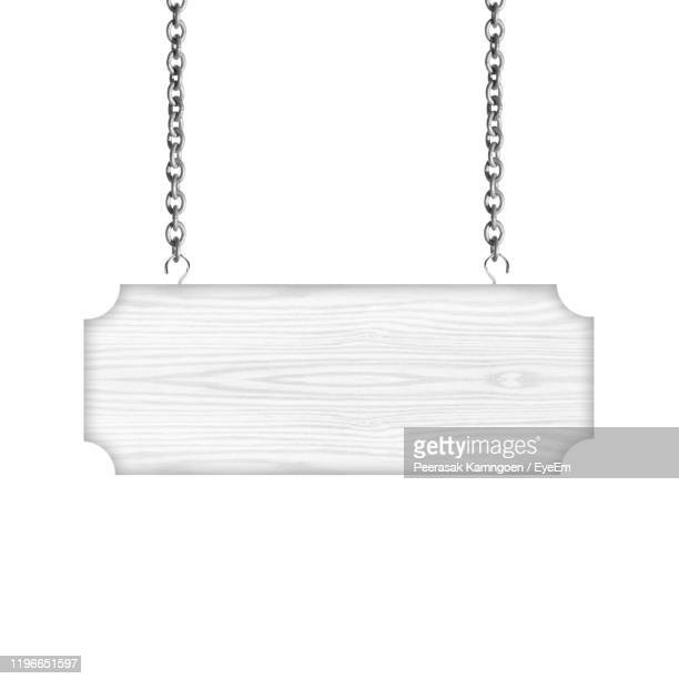 close-up of empty signboard hanging against white background - hanging sign stock pictures, royalty-free photos & images