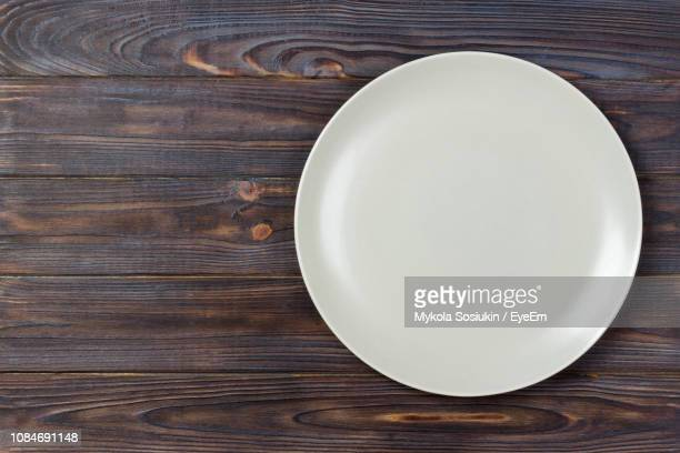 close-up of empty white plate on wooden table - plate stock pictures, royalty-free photos & images