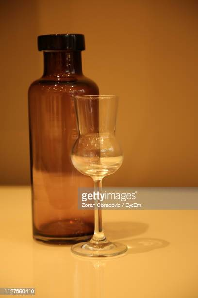 Close-Up Of Empty Wineglass And Bottle On Table