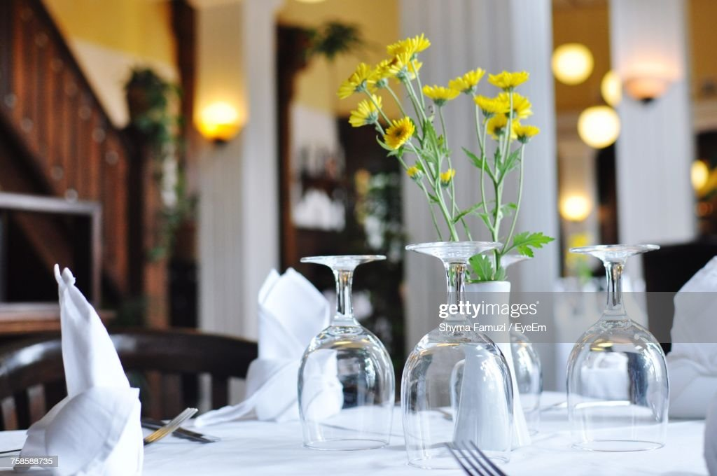Closeup Of Empty Wineglass By Flower Vase On Table At Restaurant