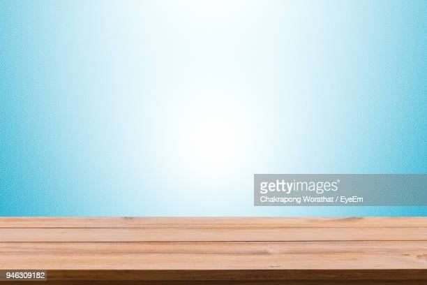 close-up of empty wooden table against blue background - blue background stock pictures, royalty-free photos & images