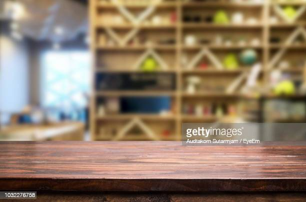 close-up of empty wooden table against shelves - 水平アングル ストックフォトと画像