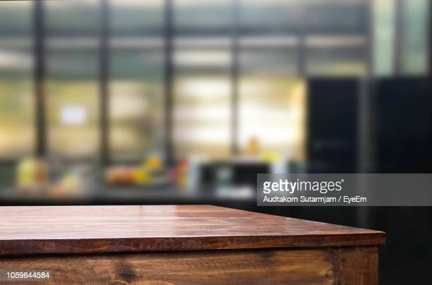close-up of empty wooden table at office - onscherpe achtergrond stockfoto's en -beelden
