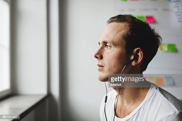 Close-up of engineer with headphones looking away in creative office
