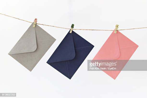Close-Up Of Envelopes Hanging On Clothesline Against White Background