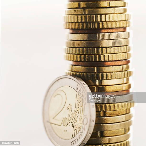 Close-up of euro coins of various denominations with two euro coin standing