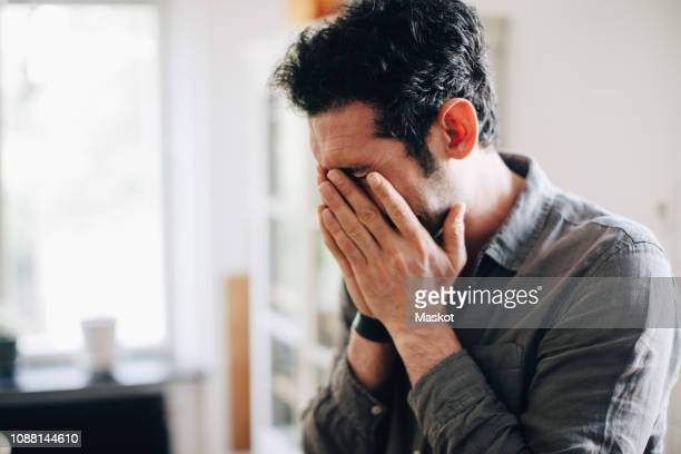 close-up of exhausted businessman covering mouth at home office - hands covering mouth stock pictures, royalty-free photos & images