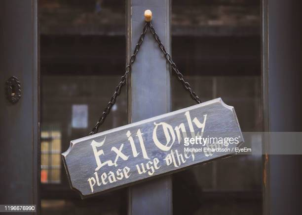 close-up of exit sign hanging on door - hanging stock pictures, royalty-free photos & images