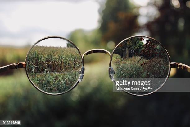 close-up of eyeglasses against grassy field - image focus technique stock pictures, royalty-free photos & images